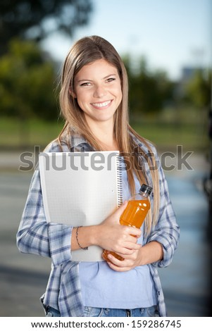 College student outdoor with drink and notebook in hand - stock photo