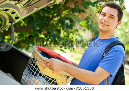 College student putting laundry in the car to go back to school - stock photo