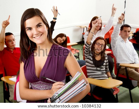 college student smiling with notebooks in a classroom - stock photo