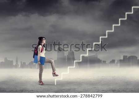 College student stepping up on stairs to gain her success