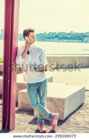 College Student Studying in New York. Wearing white shirt, jeans, sneakers, a young guy standing against pole by Hudson River, working on laptop computer, talking on phone. Instagram filtered effect. - stock photo