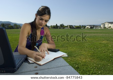 College Student studying in park with Laptop - stock photo