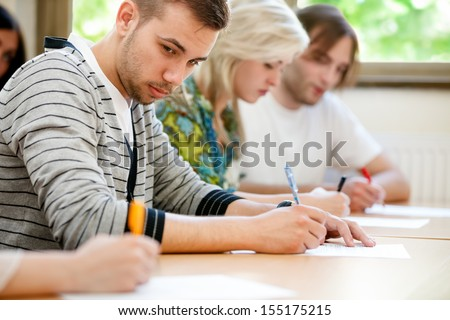 college student trying to copy off a student's test paper. - stock photo