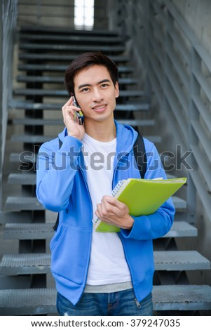 college student use mobile phone in her hand at campus - stock photo