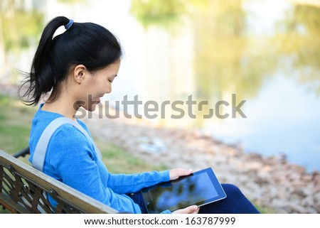 college student use tablet pc sit on bench - stock photo
