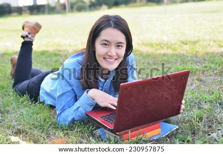 College student using laptop on campus lawn - stock photo