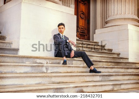 College Student Waiting Outside. Dressing in a black suit, patterned necktie, leather shoes, a young handsome businessman is sitting on stairs outside an office building, relaxing, thinking.  - stock photo
