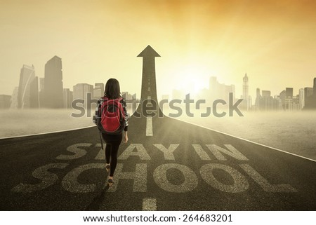 College student walking on the road turning into arrow upward with a text of Stay in School - stock photo