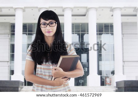 College student with long hair, standing in front of the campus building while holding a book