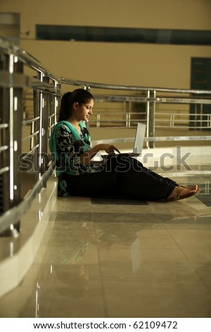 college student working on laptop at campus - stock photo