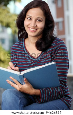 college student writing on a notebook - stock photo