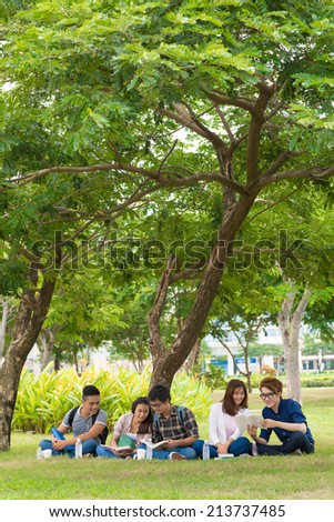 College students sitting under the tree and doing homework - stock photo