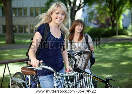 College students standing with bicycle on college campus lawn