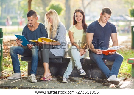 College students studying together outdoors. Three students reading and one beautiful young woman looking at camera and smiling - stock photo