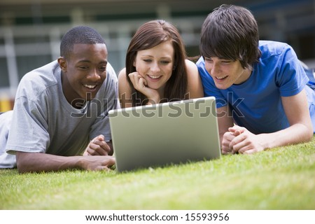 College students using laptop on campus lawn, - stock photo