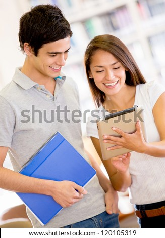 College students with a tablet computer using an app - stock photo