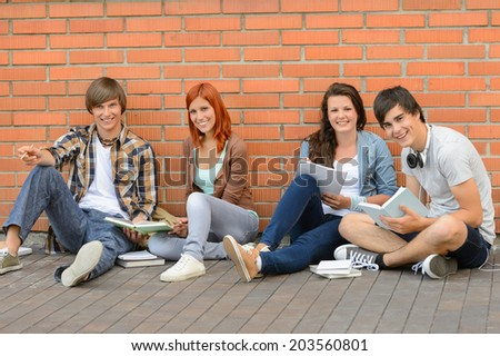 College students with books sitting ground by brick wall - stock photo