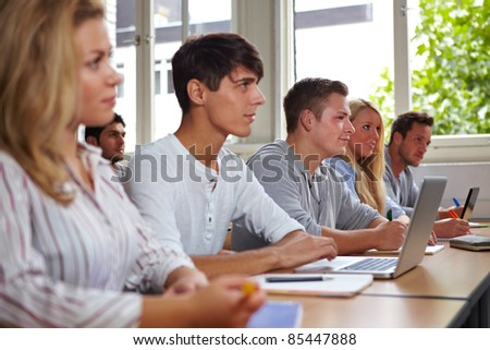 College students with laptops listening in class