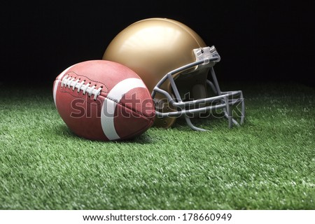 College style football and helmet on grass field against dark background - stock photo