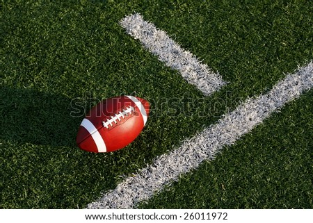 Collegiate football near the yard line - stock photo