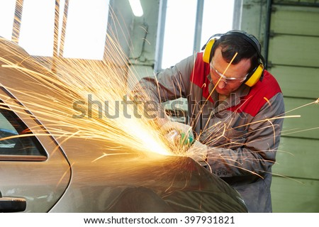 collision repairs service. mechanic grinding car body by grinder - stock photo