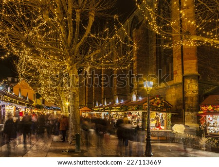 COLMAR,FRANCE-DEC 6:People walking between stand during the winter holidays season in a Christmas Market from Colmar in Alsace,France on December 6, 2013.Colmar is the capital of Alsatian wine. - stock photo
