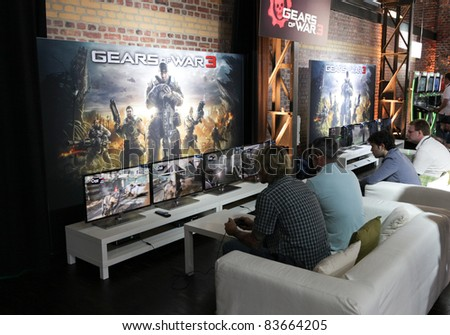COLOGNE - AUGUST 16: Videogamers playing Gears of War 3 at GamesCom 2011, the most important European video games Expo August 16, 2011 in Cologne, DE - stock photo