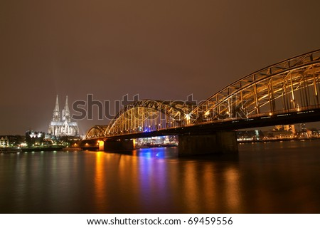 Cologne cathedral with Hohenzollern bridge at night - stock photo