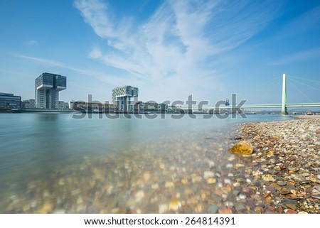 Cologne city skyline at the rhine shore with bridge and crane houses - stock photo