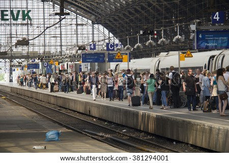 Cologne, Germany - August 30, 2013: People waiting for their train on a platform in the historic railway station of Cologne, Germany on August 30, 2013