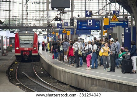 Cologne, Germany - August 30, 2013: People waiting for their train on a platform in the historic railway station of Cologne, Germany on August 30, 2013 - stock photo