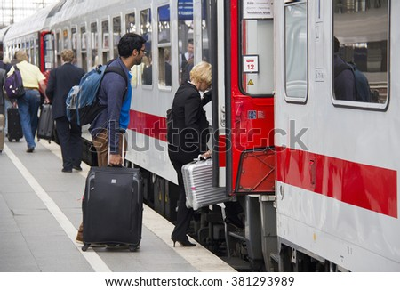 Cologne, Germany - August 30, 2013: People with luggage get into an international train on a platform in the historic railway station of Cologne, Germany on August 30, 2013 - stock photo