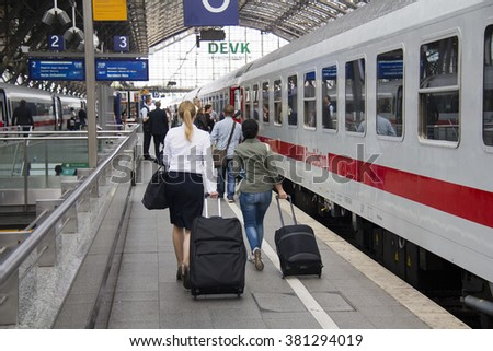 Cologne, Germany - August 30, 2013: People with luggage walk to an international train on a platform in the historic railway station of Cologne, Germany on August 30, 2013 - stock photo