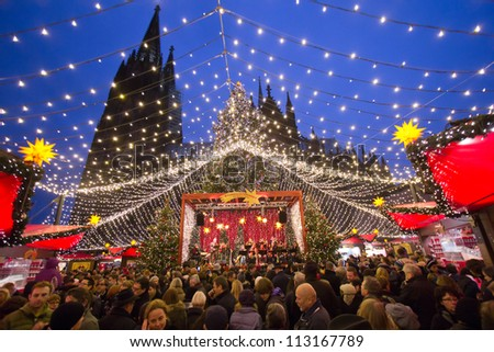 COLOGNE, GERMANY - DECEMBER 23: People at a Christmas market on December 23, 2011 in Cologne, Germany. The history of these markets goes back to the Late Middle Ages in the German part of Europe. - stock photo