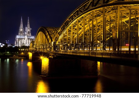 Cologne Gothic Cathedral and bridge at night - stock photo