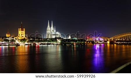 Cologne panorama at night. Cathedral, Railroad bridge and Great St. Martin Church included - stock photo