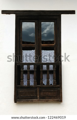 Colombia, Beautiful white villa with shingle roofs hidden behind walls in colonial Villa de Leyva. Old style window - stock photo