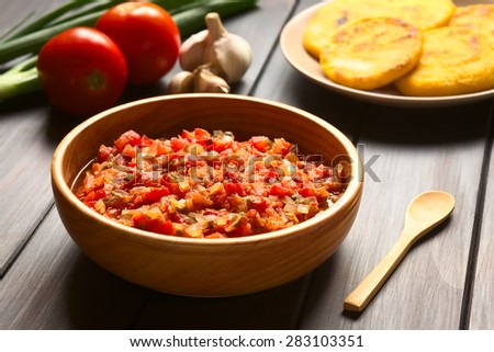 Colombian hogao or criollo sauce (salsa criolla) made of cooked onion, tomato, served as accompaniment, photographed on dark wood with natural light (Selective Focus, Focus in the middle of the sauce) - stock photo