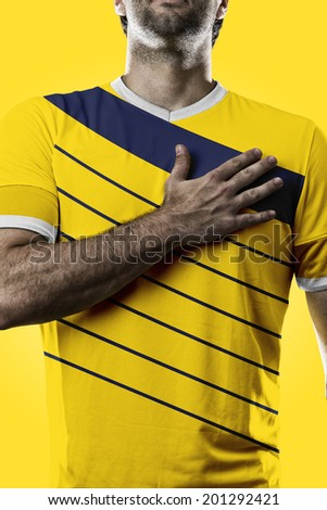 Colombian soccer player, listening to the national anthem with his hand on his chest. On a yellow background. - stock photo