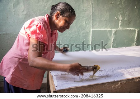 COLOMBO, SRI LANKA - MARCH 12, 2014: Local woman working on batik. The manufacture and export of textile products is one of the biggest industries in Sri Lanka. - stock photo