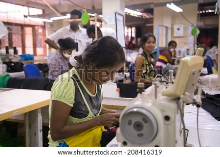 COLOMBO, SRI LANKA - MARCH 12, 2014: Local women working on sewing machine in apparel industry. The manufacture and export of textile products is one of the biggest industries in Sri Lanka. - stock photo