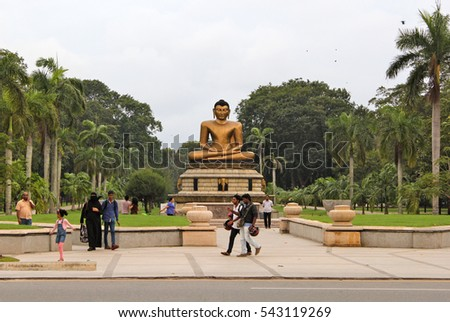 COLOMBO, SRI LANKA-NOV. 30, 2014:  Locals walk past the huge Buddha Statue at the entrance to Viharamahadevi Park,   in the city center.  It is the oldest park of the Port of Colombo.