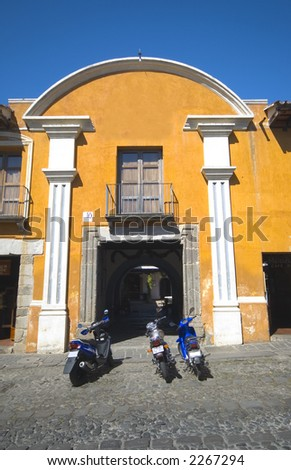 colonial building hotel with motorbikes antigua guatemala - stock photo