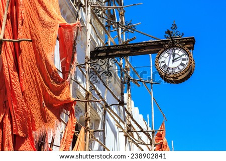 Colonial clock hanging on an old colonial building in Stone Town, Zanzibar - stock photo