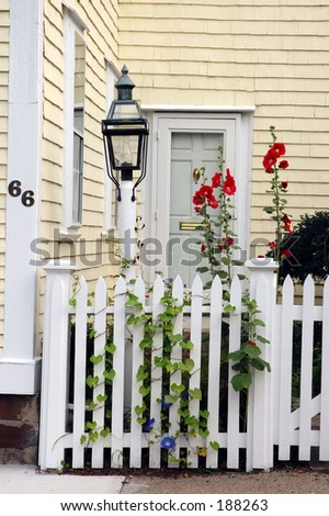 Colonial house entranve with front fence and small garden
