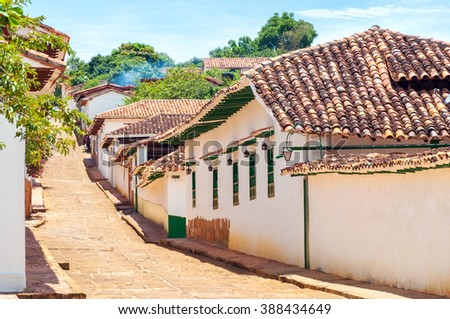 Colonial street with with white historic buildings in Barichara, Colombia - stock photo