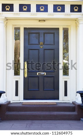 Colonial style black door on white house with  gold ornamentation above - stock photo
