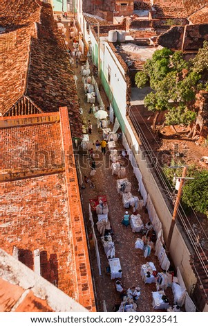 Colonial town cityscape of Trinidad, Cuba. Street shopping. Many little street shops sell linen and cotton clothes and accessories. UNESCO World Heritage Site. - stock photo