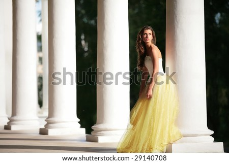 colonnade of the old-time building and gorgeous bride in the white-golden gown
