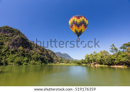 color air balloon over the green lake  with mountain and blue sky